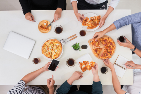 The office staff eat pizza and drink coffee in the business office. They have a break in their work. They are resting. Banque d'images - 102932000