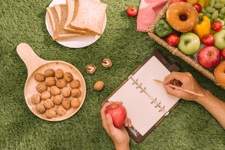 Picnic wicker basket with food, bread, fruit and orange juice on a red and white checked cloth in the field with green nature background. Picnic concept.