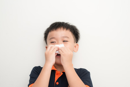 Cute little boy sneezing in tissue on white background Stock Photo