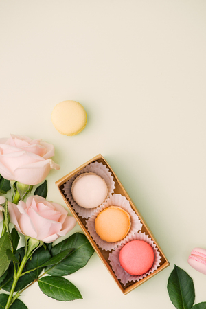Colorful macaroons and rose flowers on light green. Sweet macarons in gift box. Top view