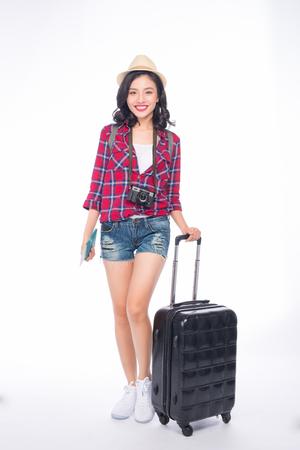 Viaje de mujer. Joven hermosa mujer asiática viajero con maleta y cámara sobre fondo blanco.
