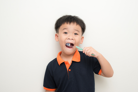 Little boy brushing his teeth on white background Stock Photo