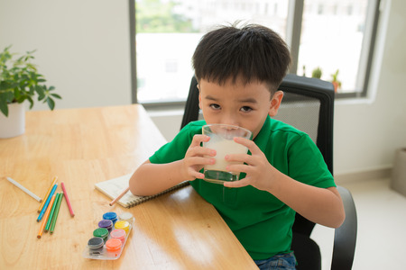 School child doing homework and drinking milk Stockfoto