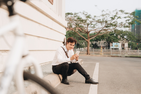 Fashionable young bearded man using a digital tablet , cheerfully smiling, watching or reading something funny, sitting on the ground, near the bicycle, outdoors. Standard-Bild - 103390172
