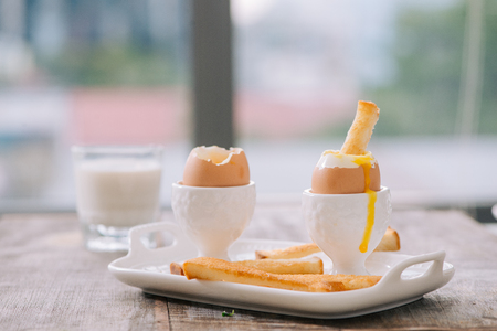 delicious breakfast with soft boiled eggs and crispy toasts, closeup