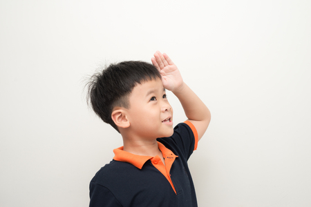 Cute little boy showing a saluting gesture in the studio