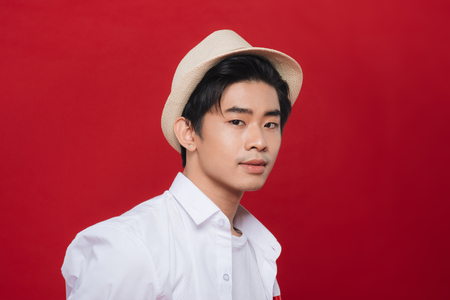 Attractive young asian man having fun on red background. Stylish outlook, hat, happy, expressing true positive emotions, funny.