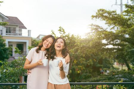 Dos mujeres relajándose en el jardín de la azotea tomando café Foto de archivo