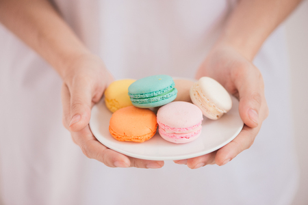 Hands holding colorful pastel cake macarons or macaroons