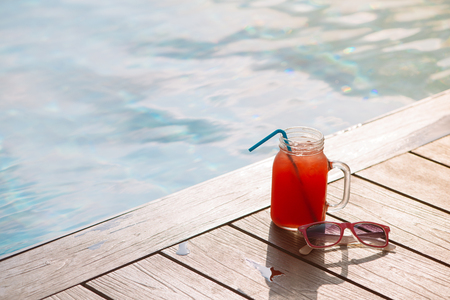 Glass of fresh watermelon smoothie juice drink on border of a swimming pool - holiday tropical concept Banco de Imagens