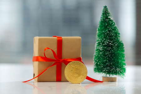Christmas gift or New Year with ribbon and little fir and best gift bitcoin coin on light background. Cryptocurrency investition concept
