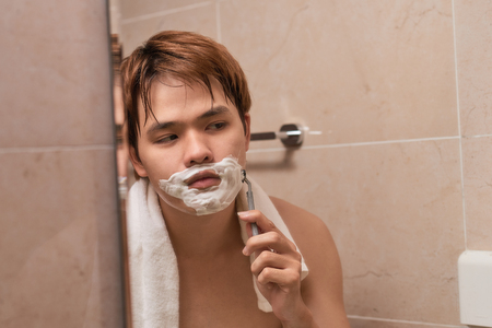 Handsome young asian man is shaving his face and looking at the mirror.