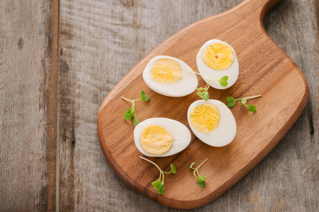 Boiled eggs on cutting board. Selective focus, space for text
