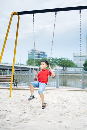 Happy asian boy swinging at the playground in the park 免版税图像