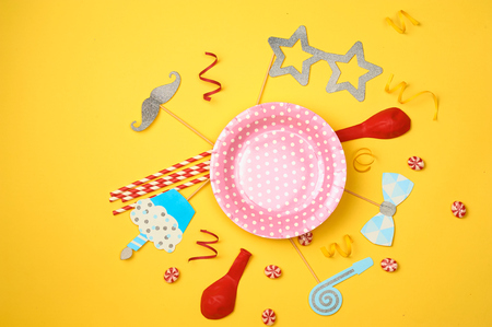 Colored party, sweets and confetti on yellow background top view mockup
