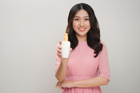 health and beauty concept - happy woman with skincare package
