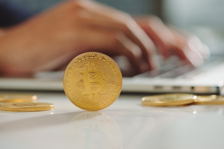 Gold bitcoin over office desk. Bitcoin payment concept.
