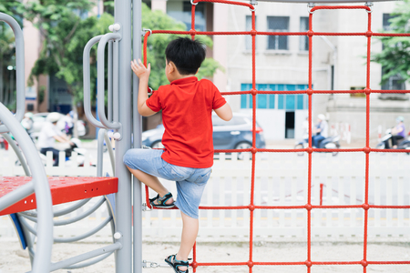 Young asian boy climb on the red rope fence and gray bar by his hand to exercise at out door playground under the big tree.