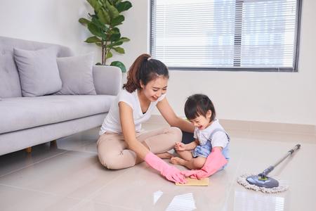 maman enseignant fille nettoyant leur salon à la maison le week-end. Une jeune femme et une petite fille enfant époussetant. travaux ménagers familiaux et concept de ménage.