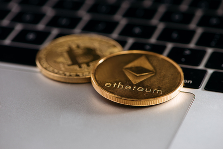Digital currency in the information era: shiny bitcoin coins on a laptop