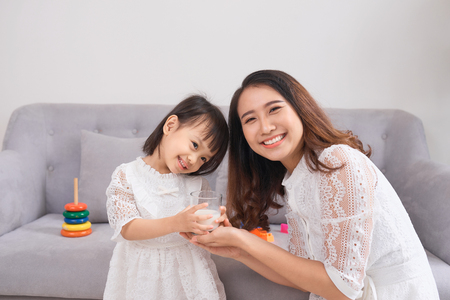 Little girl and her mom drinking milk sitting on sofa at home. Motherhood and care, healthy eating and lifestyle, early development concept, copy space Stok Fotoğraf