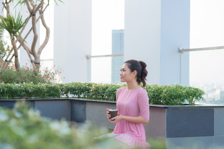 Young woman drinking coffee in a cafe outdoors.Image of happy female in open air cafe looking at camera in urban environment.