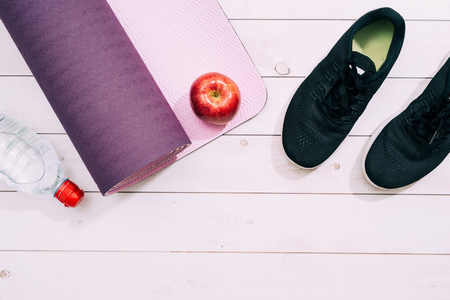 Ladies Sports Accessories such as trainers shoes, dumbbells, yoga mat with water and apple. Fitness, sport and healthy lifestyle concept. Top view, copy space