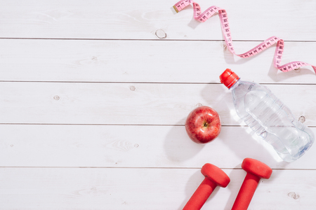 fitness concept with dumbbells and red apple - sport and leisure Stock Photo