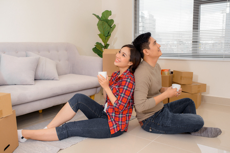 mortgage, people and real estate concept - happy couple with boxes moving to new home and drinking coffee