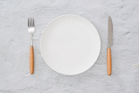 Table prepared for reservation. Arranged fork, knife and plate along with a towel in a restaurant Foto de archivo - 104345517