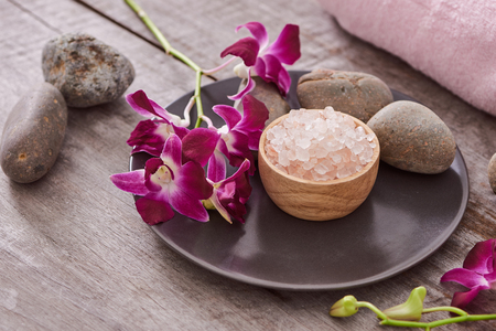 bath salt at bamboo bowl and orchids flowers on dark wood