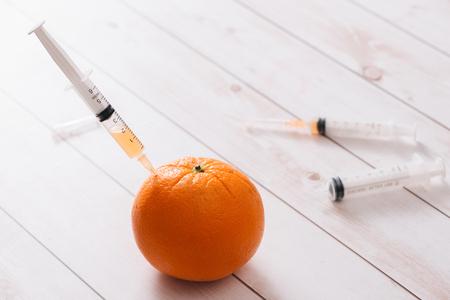 Syringe of orange on a white background isolation Banque d'images