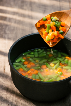 Vegetable stew in gray pot on color napkin on wooden background Stock Photo