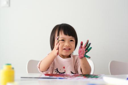 Piccola pittura asiatica della ragazza con il pennello e le vernici variopinte