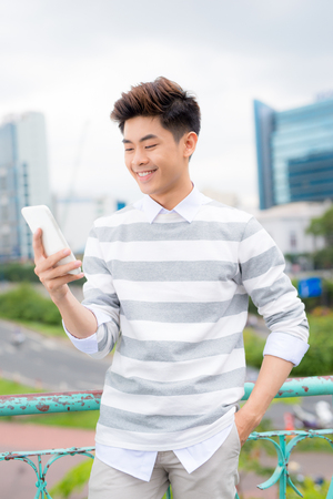Young asian handsome businessman smiling while reading his smartphone. Portrait of asian business man reading message with smart phone in outdoor. 版權商用圖片 - 104538883