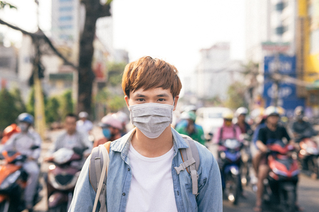 Hombre asiático joven que vive en la ciudad con aire contaminado