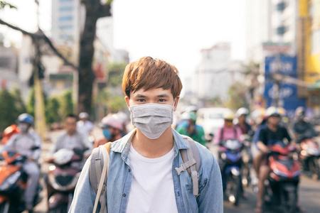 Jonge Aziatische man die in stad met vervuilde lucht leeft