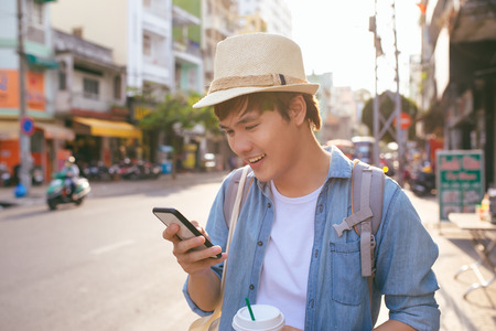 Smiling handsome young man drinking coffee and using smart phone