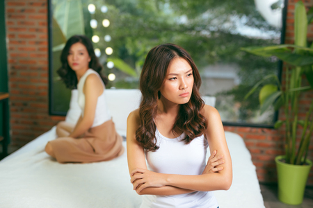 Two young beautiful women angry with each other at home