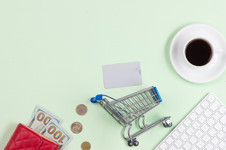 Online shopping concept. Computer keyboard, shopping cart and coffee with copy space.