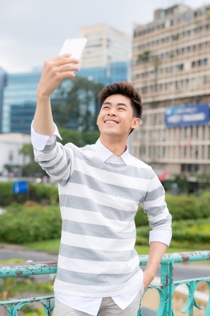 Cheerful Asian man taking selfie on modern smartphone while enjoying pleasant walk in public park, portrait shot