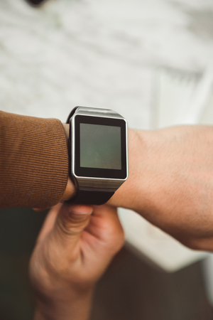 Young man wears smart watch working on table