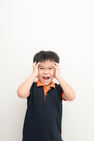 Cute little boy covering ears with hands, on white background