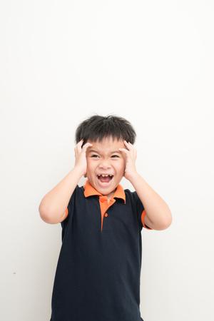 Cute little boy cubriendo los oídos con las manos, sobre fondo blanco.