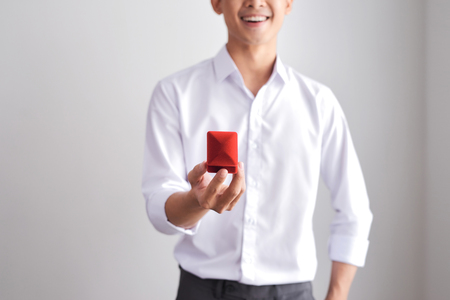 Handsome elegant man in a white shirt is holding a box with an engagement ring and shows in camera.