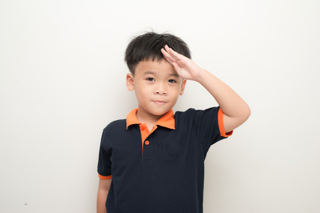Cheerful little boy putting a hand on the forehead greeting, isolated on a white background. 写真素材 - 105191580