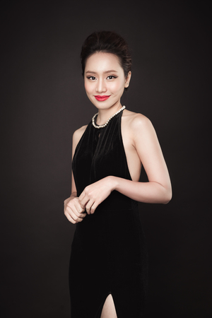 Partij. Mooie Aziatische vrouw op zwarte achtergrond. Stockfoto