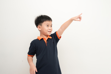 Close up portrait of cute boy pointing with finger into the distance. isolated on white background. Foto de archivo