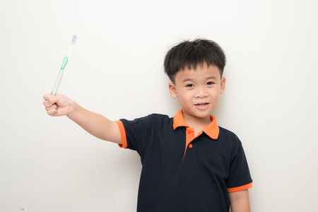 Cheerful little boy holding a tooth brush over white background, Studio portrait of a healthy mixed race boy with a toothbrush isolated.