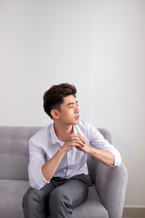 Young asian man sitting on couch and looks thought something, isolated on white